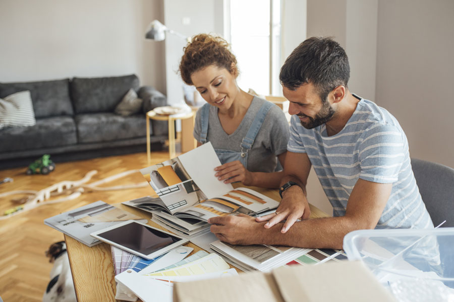 couple sitting at kitchen table with iPad and brochures planning a remodel